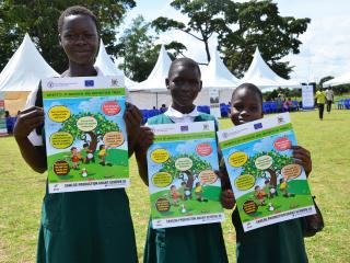 Students of Ngetta Girls' Primary School hold up posters on benefits of tree planting