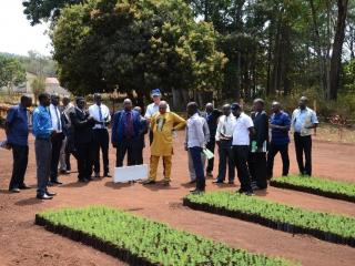 Participants of the SPGS III Steering Committee meeting listen to a student of Nyabyeya Forestry College talk about the College's tree nursery